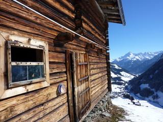 Almhütte mit Gebirge im Hintergrund