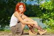 beautiful woman sitting on shore of lake