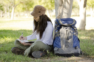 Young beautiful woman writing on travel journal