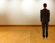 Business man standing near white wall