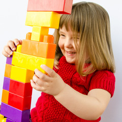 Happy little girl plays with colorful plastic blocks