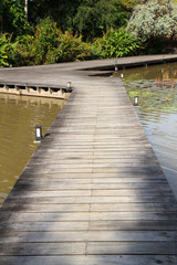 a wooden plank boardwalk on the pond to summerhouse in a garden