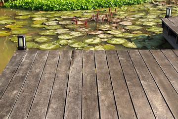 a wooden plank boardwalk on the pond to summerhouse in a garden