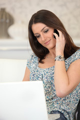 woman with computer on the phone