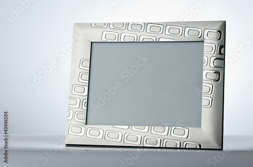 Blank silver picture frame at the table with place for your own