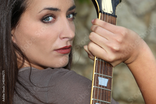 Woman holding her electric guitar behind her back