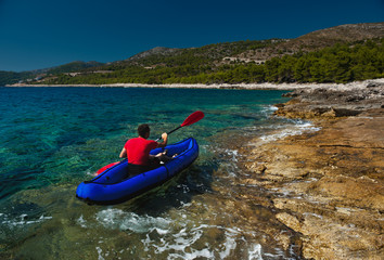 Man rowing in inflatable kayak at Adriatic sea. Hvar, Croatia