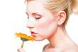 junge blonde Frau riecht an einer Blume