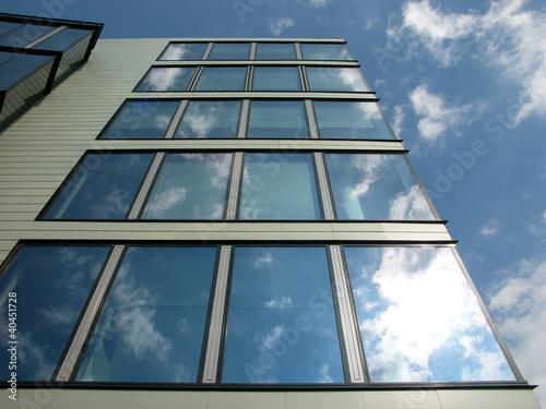 Wolkenspiegelung in der Glasfassade eines Bürogebäudes