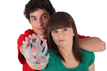 boy and girl holding the at symbol