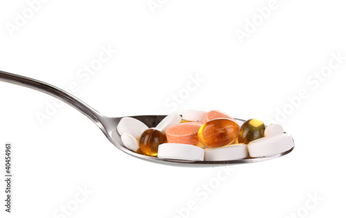 Spoon with pills isolated on white