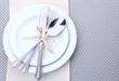 White empty plates with fork, spoon and knife tied with a ribbon