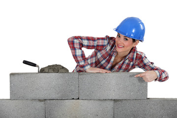 portrait of young female bricklayer pointing at concrete wall