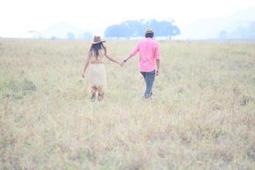 man and women wearing a hat walking in the grass field