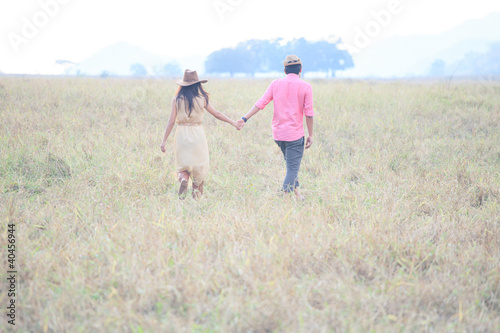 man and women wearing a hat walking in the grass field