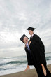 A guy and his girlfriend rejoicing their graduation by giving her a piggy back ride.