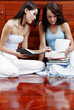 Two ladies sitting on the floor doing revision together.
