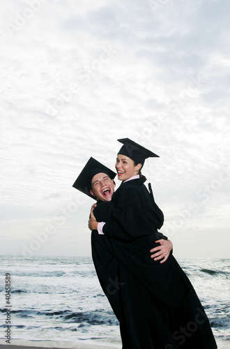 An elated guy and lady in a robe and mortar board rejoicing their graduation on the beach.