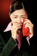 A lady in formal suit wiping her tears with a red handkerchief.