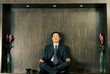 A man in business suit meditating.