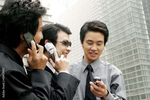 Three men in office attires using handphones.