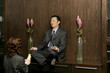 Woman worshipping a businessman who is sitting on the shelf meditating.