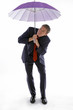 Man in business suit holding an umbrella while checking the weather.