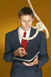 Businessman reading a document with a rope hanging around his neck.