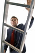Man in business suit climbing up a ladder.