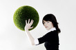 Businesswoman holding a grass ball.