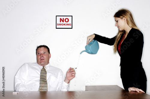 Businesswoman watering the cigarette from an ignorant businessman.