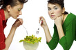 Two women sharing a bowl of salad.