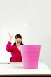 Businesswoman throwing a crumpled paper into a dustbin.