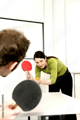 Businessman and businesswoman playing table tennis.