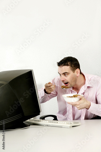 Businessman checking his work while eating breakfast cereal.