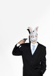 Businessman with rabbit mask pointing a pistol at himself.