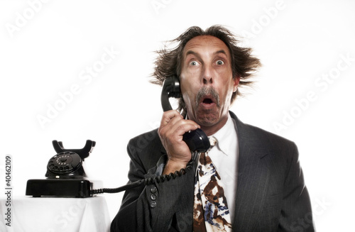 Businessman receiving a shocking phone call.