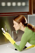 Woman text messaging while washing dishes in the kitchen.
