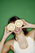 Woman covering her eyes with cut oranges.