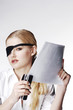 Businesswoman with eye patch stapling papers.