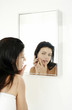 Woman checking her face on the mirror