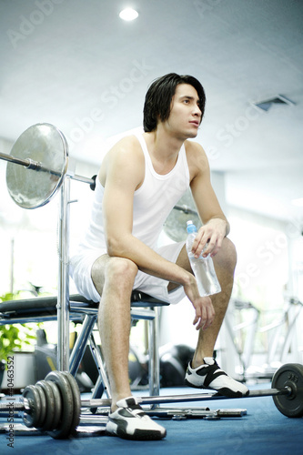 Man sitting in gym holding a bottled water