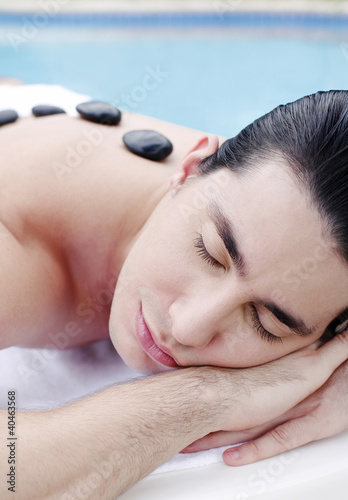 Man lying forward with therapeutic hot stones on his back