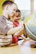 Boy and girl referring to a globe