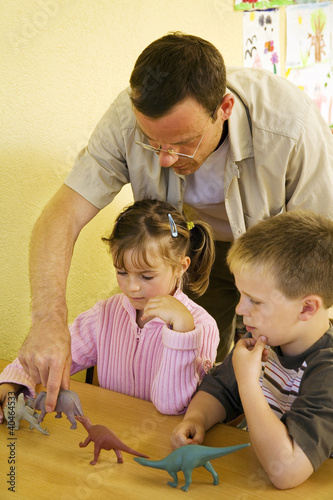 Male teacher showing his students some dinosaur figurines