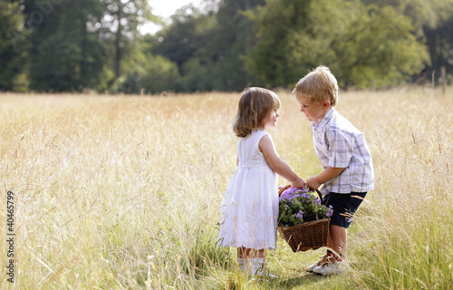 Little boy helping little girl with the basket of flowers