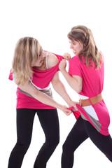 Zwei junge Frauen streiten wegen dem gleichen Kleid
