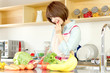 Beautiful young woman in kitchen making salad. Portrait of asian