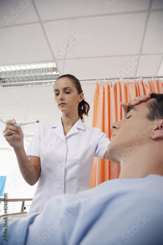 Nurse checking man's temperature