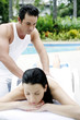 Woman getting a body massage at the pool side